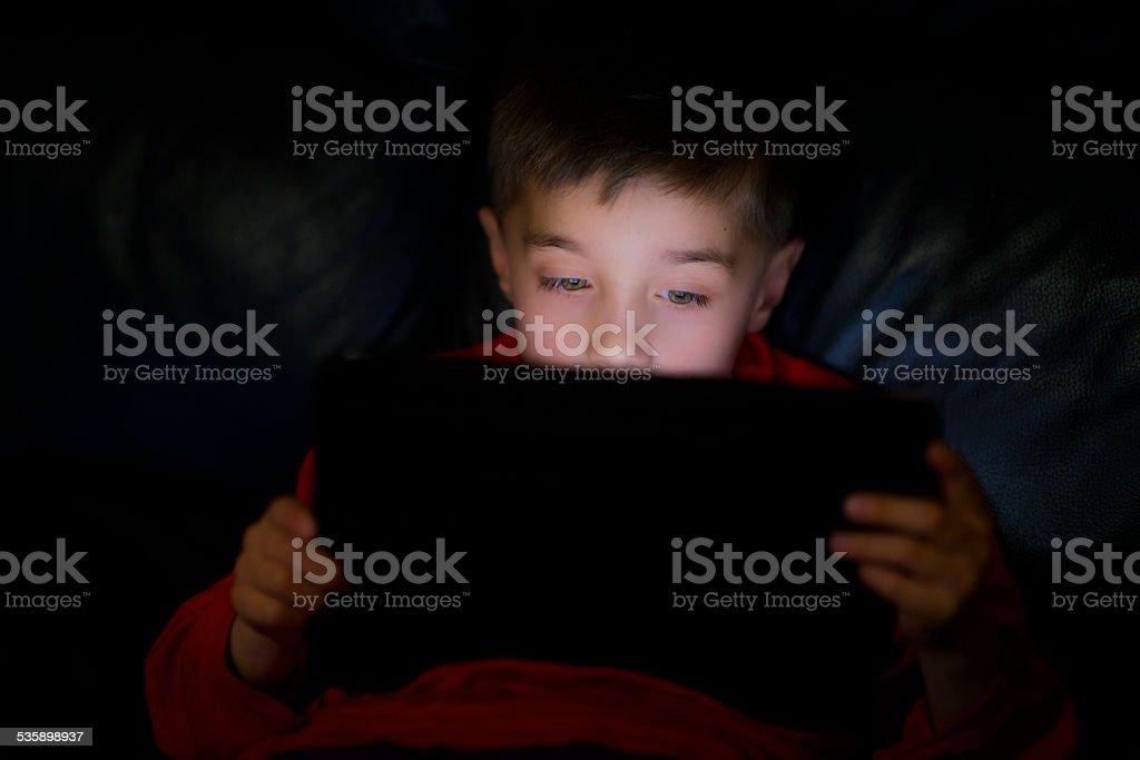 Kind liest von seinem tablet in the dark – Foto