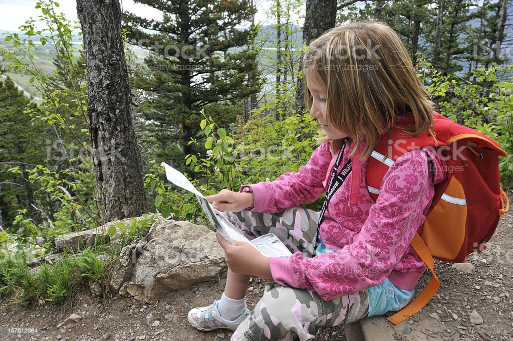 Child reads map while on hike in the woods stock photo