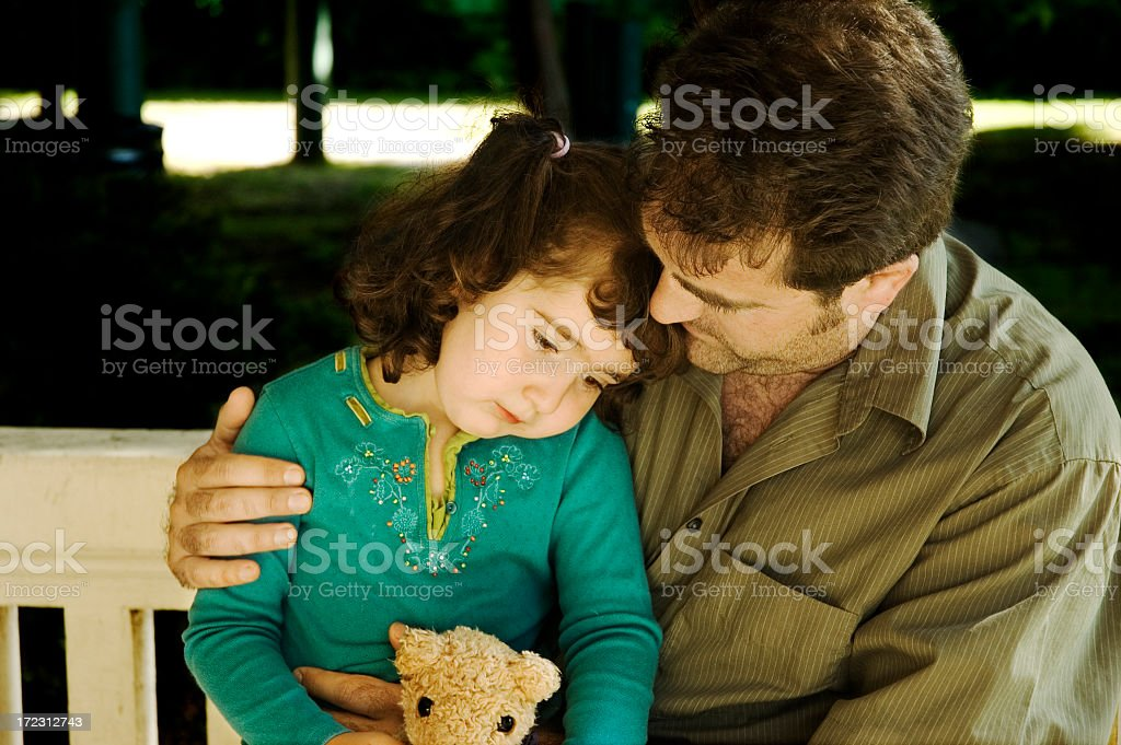 Child receiving comforting hug while holding teddy bear royalty-free stock photo