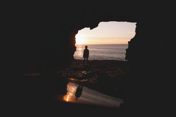 Child reflected in a sea cave. stock photo