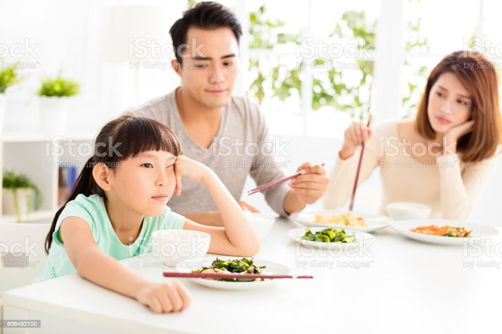 child refuses to eat while family dinner stock photo