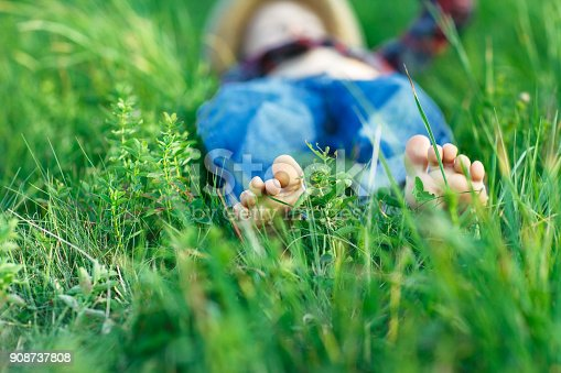 112301234 istock photo Child relaxing in grass on field. Focus on foot 908737808