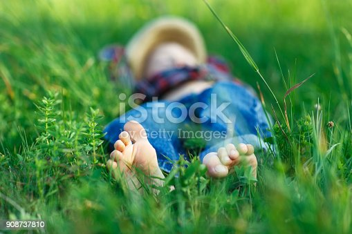 112301234 istock photo Child relaxing in grass on field. Focus on foot 908737810