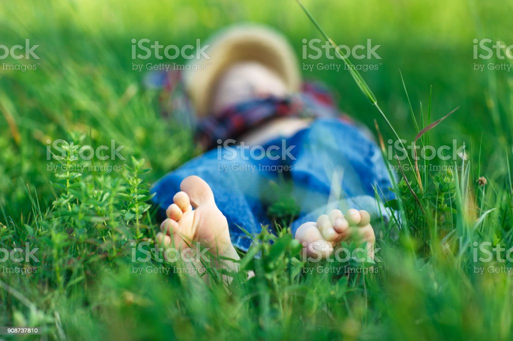 Child relaxing in grass on field. Focus on foot stock photo