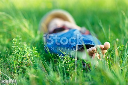 112301234 istock photo Child relaxing in grass on field. Focus on foot 908737814