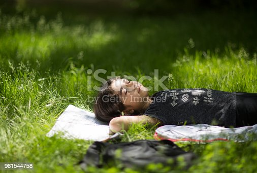 112301234 istock photo Child relaxing in grass on field. 961544758