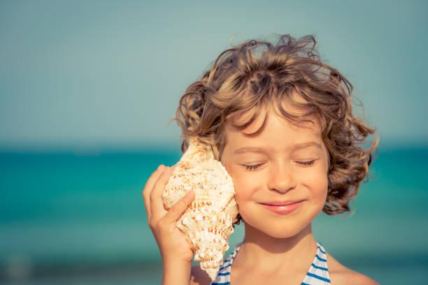 Criança relaxante na praia - foto de acervo