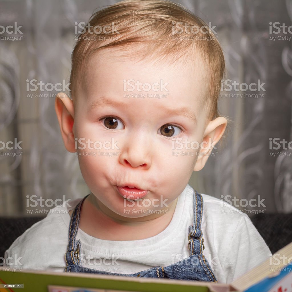 Child repeats sounds from audio book stock photo