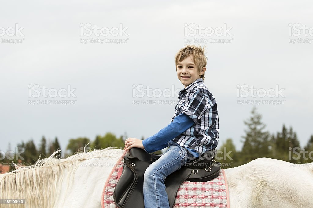 Child riding a horse outdoors royalty-free stock photo