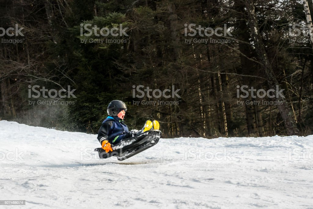 A child riding a sledge downhill and jump in mid air. stock photo
