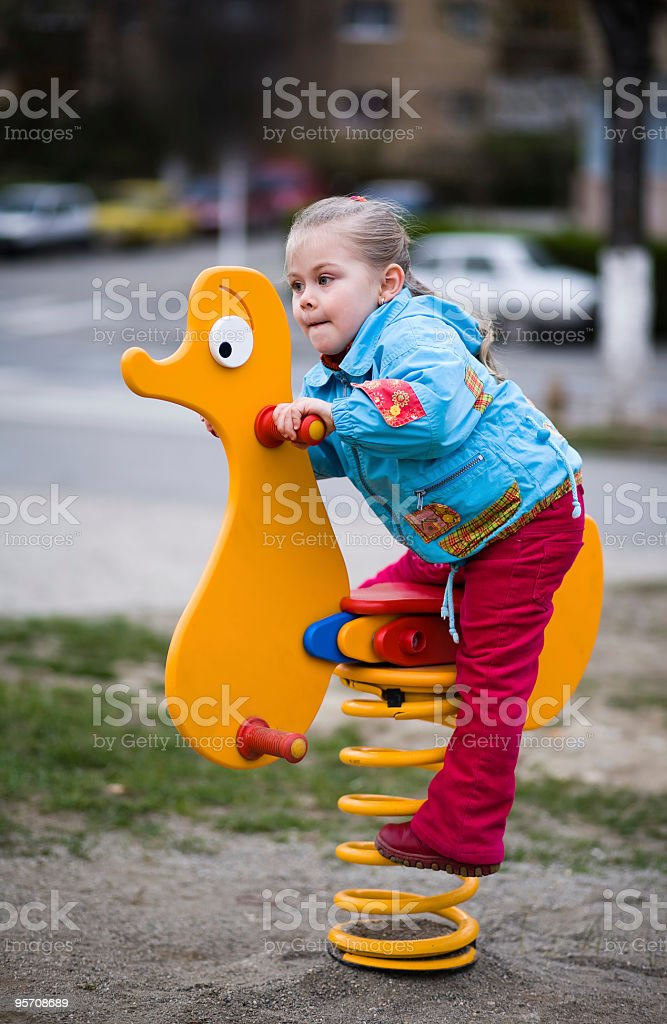 Child riding a spring horse in amusement park stock photo