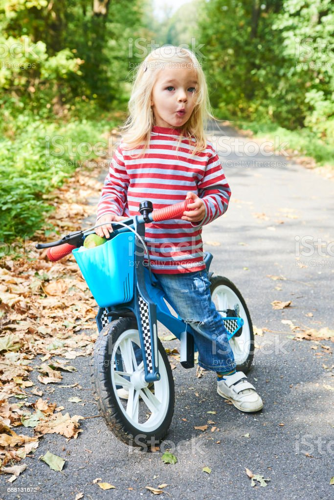 Child riding balance bike. Kid on bicycle in sunny park. Little girl ride glider bike on warm summer day. Preschooler learning to balance on run bicycle. Sport for kids stock photo
