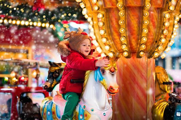 child riding carousel on christmas market - karussell stock-fotos und bilder