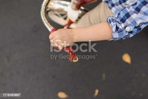 A 3-year-old boy riding his red vintage tricycle barefoot on a Spring day in South Florida. With a focus on the child's hand gripping the handlebar.