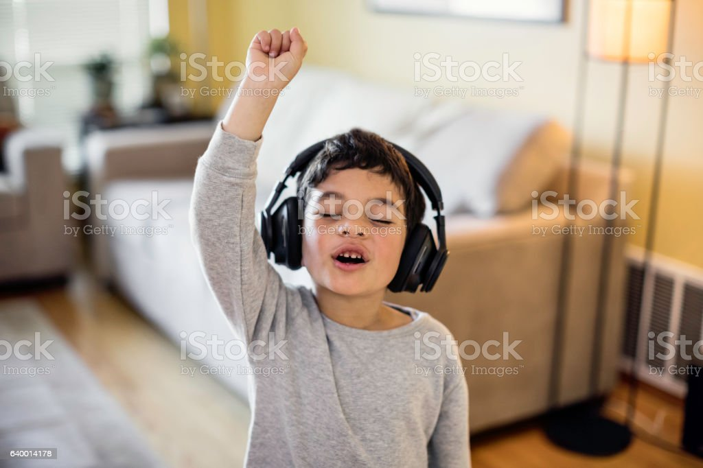 Child Rocking Out to Music Stock photo of a child listening to music on wireless headphones 4-5 Years Stock Photo