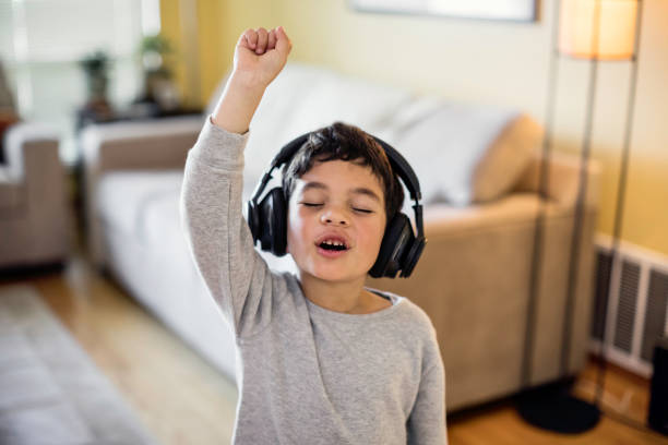 Child Rocking Out to Music Stock photo of a child listening to music on wireless headphones wireless headphones stock pictures, royalty-free photos & images