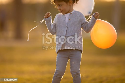 istock Child running and holding balloons 1138269297