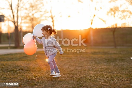 istock Child running and holding balloons 1138269362