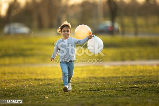 istock Child running and holding balloons 1138269373