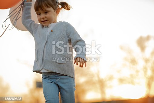 istock Child running and holding balloons 1138269393