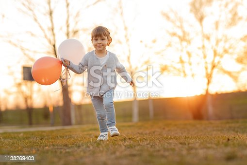 istock Child running and holding balloons 1138269403