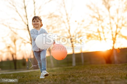 istock Child running and holding balloons 1141295471