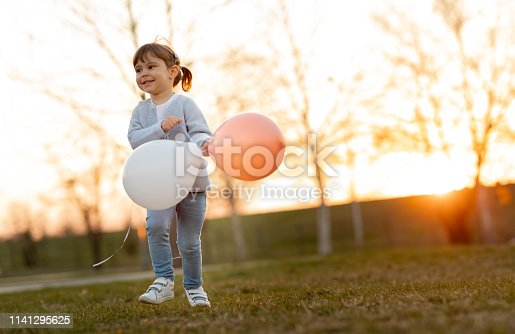 istock Child running and holding balloons 1141295625