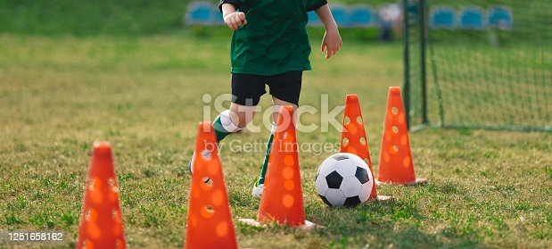 621475196 istock photo Child running soccer ball between training cones. European football sports summer camp for junior level athletes. Soccer kid with ball on grass pitch. Soccer goal and bench in the background 1251658162