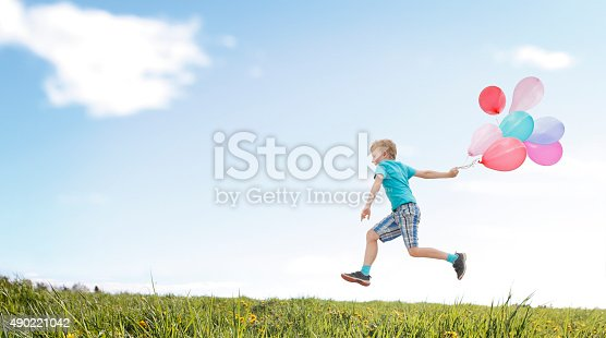 Happy boy running with balloons over the meadow. See more of this little boy:  http://www.oc-photo.net/FTP/icons/nurvic.jpg