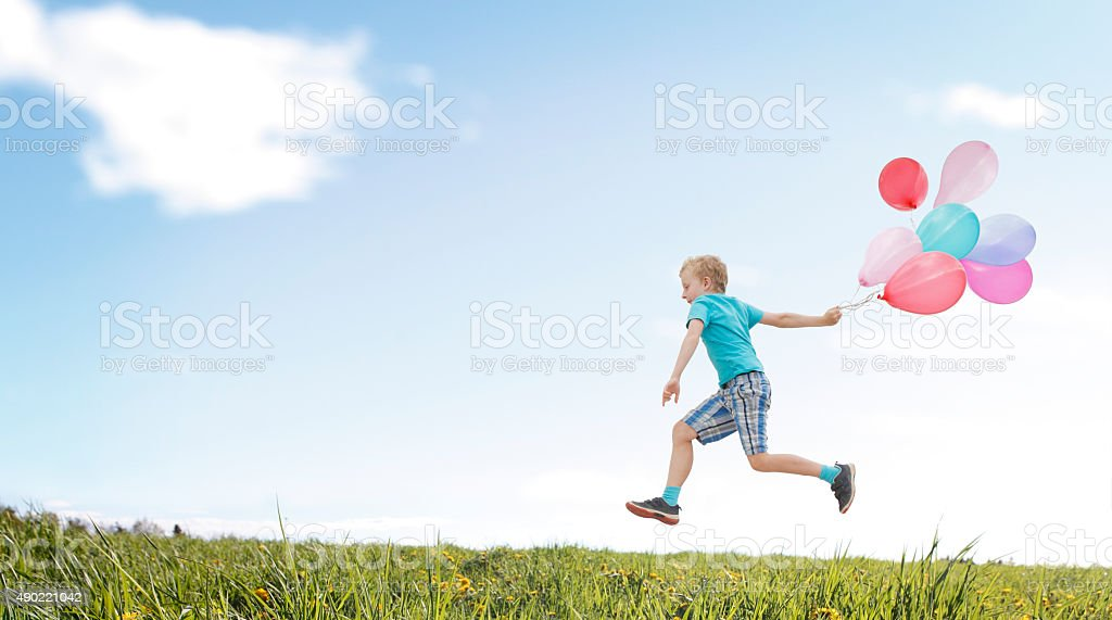 Child running with balloons over the meadow stock photo