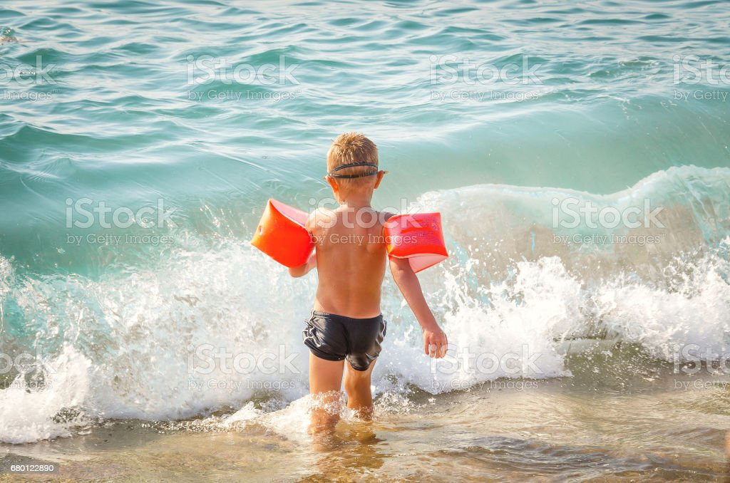 child runs in the sea with protective inflatable sleeves stock photo