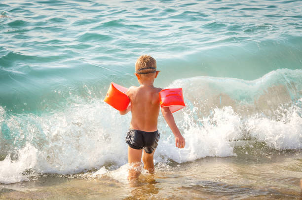 child runs in the sea with protective inflatable sleeves - swim arms imagens e fotografias de stock