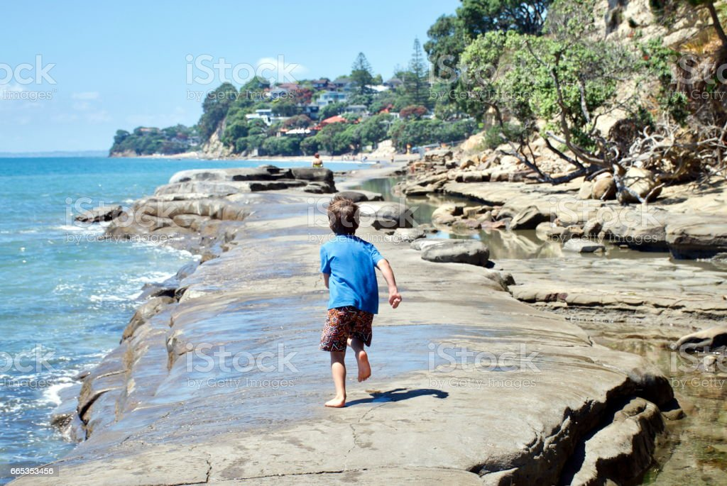 A Child Runs on a Concrete Walkway in the Sea stock photo