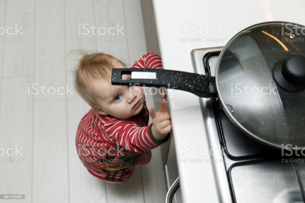 Kindersicherheit im Wohnkonzept - Kleinkind für Pfanne auf dem Herd in der Küche zu erreichen – Foto