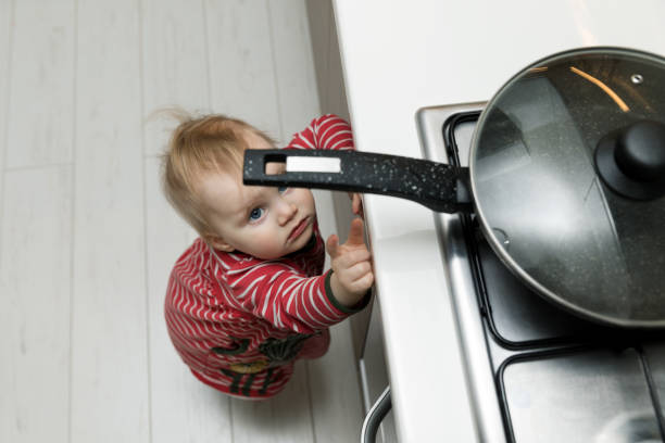 child safety at home concept - toddler reaching for pan on the stove in kitchen - burning stock pictures, royalty-free photos & images