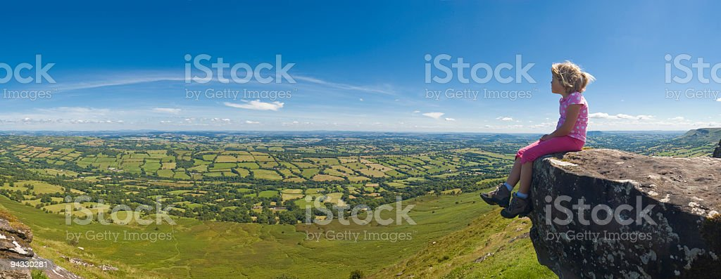 Child sat on mountain looking over panoramic view to blue royalty-free stock photo