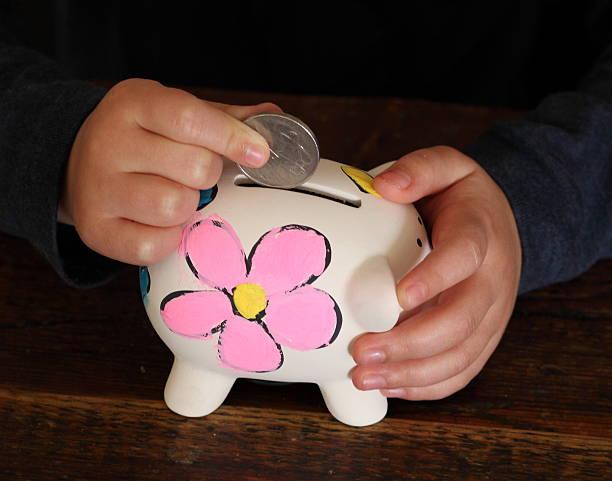 Child Saving money in piggy bank stock photo