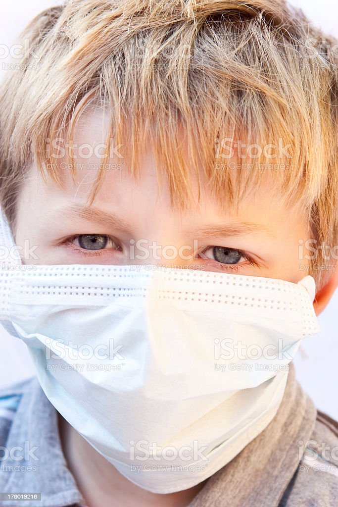 Child scared of catching germs wearing surgical face mask royalty-free stock photo
