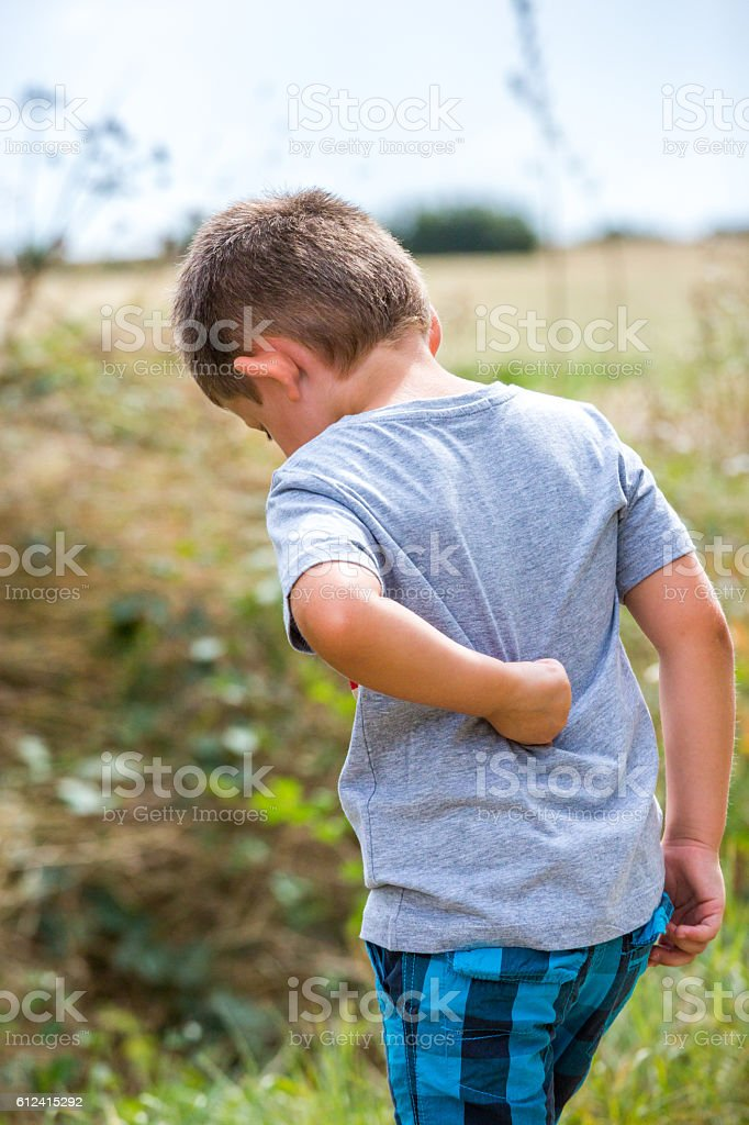 child scratching his back on a country road stock photo