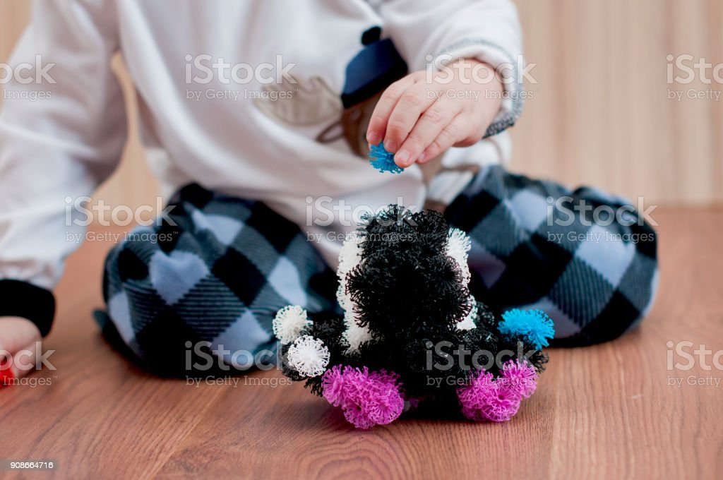 child sculpts a machine from a velcro constructor stock photo