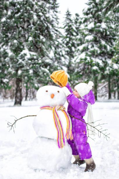 kindes formt einen schneemann in einem verschneiten park. winter-outdoor-aktivitäten - schneemann bauen stock-fotos und bilder