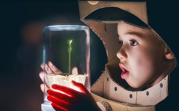 kind hält eine sprießen - erforschung des weltalls stock-fotos und bilder