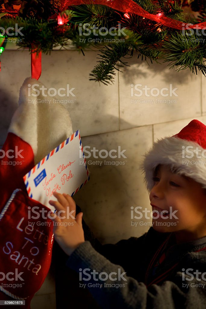little child smiling and send letter for Santa in the north pole