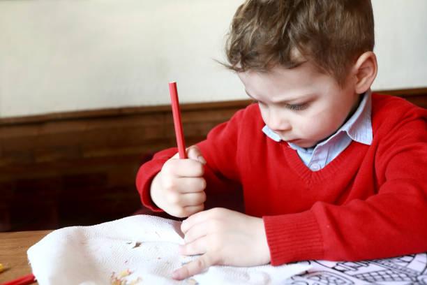 El niño afila el lápiz - foto de stock