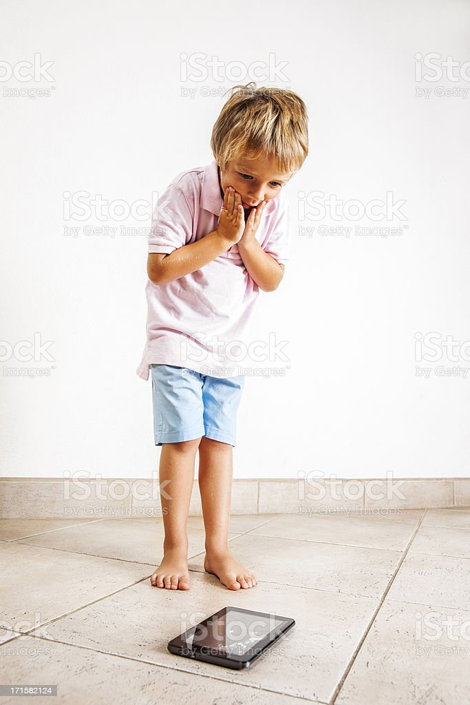 Child shocked after he has dropped and broken a tablet stock photo