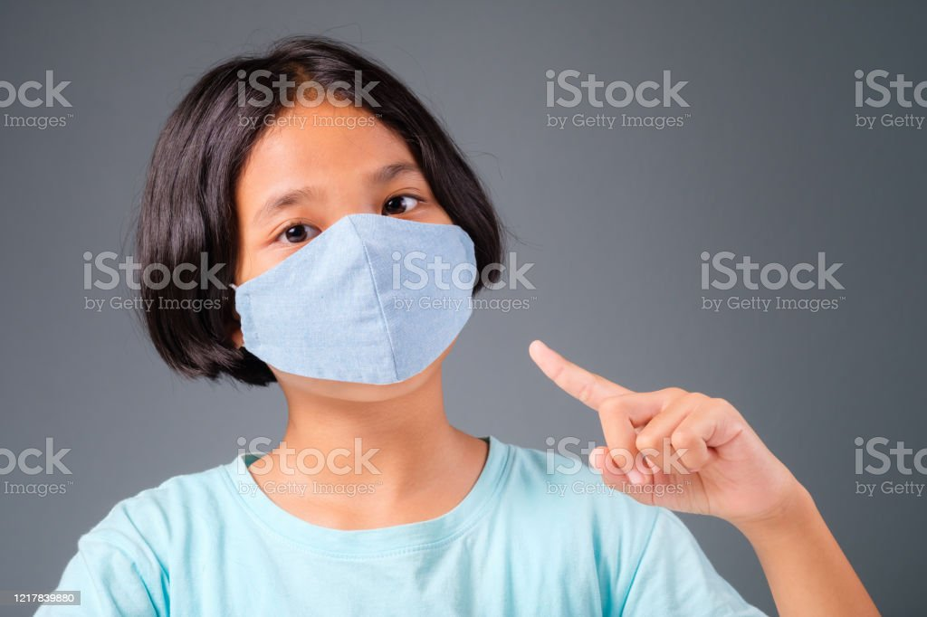 Child Show Wearing Mask Asian nine years old girl present wearing hygienic cloth mask to prevent the virus Asian and Indian Ethnicities Stock Photo