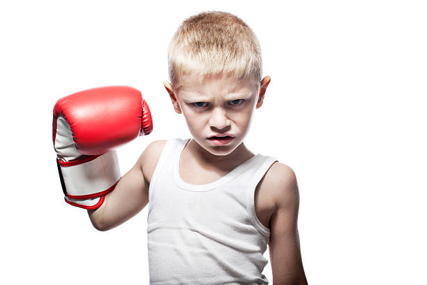 Child showing his muscles with boxing gloves stock photo