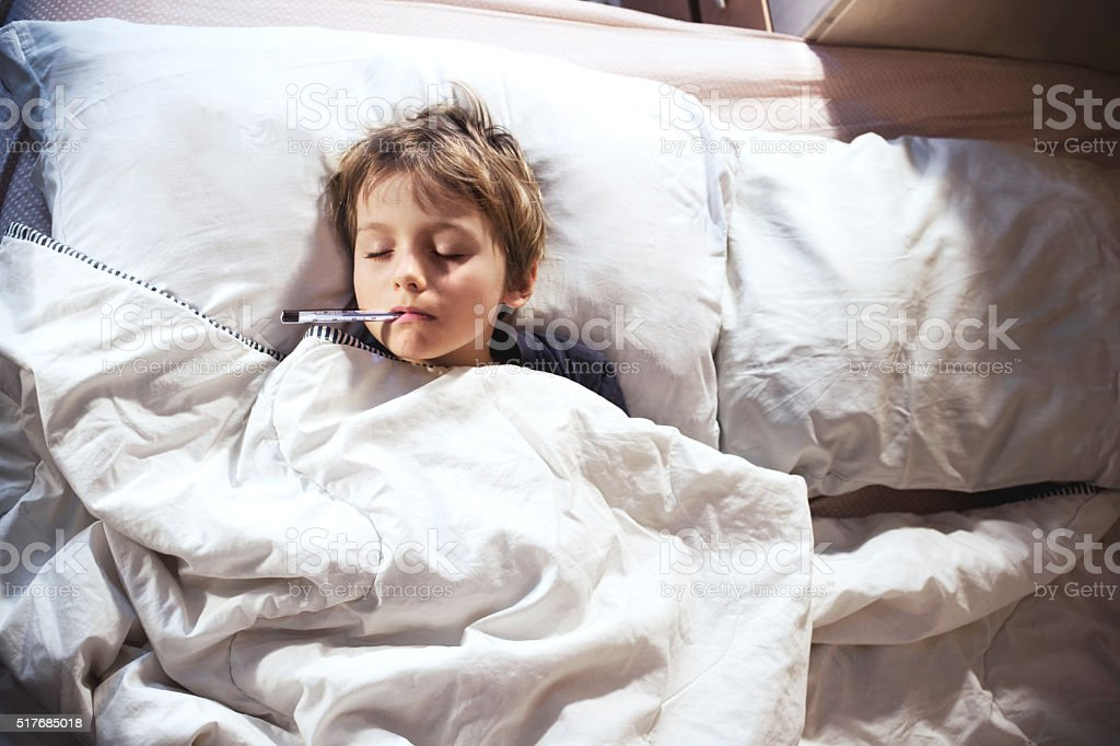 child sick in bed with fever and thermometer