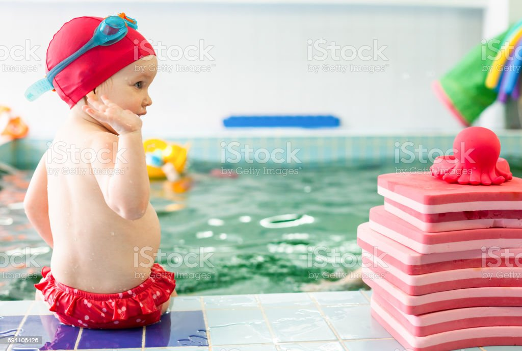 Child sitting at swimming pool stock photo