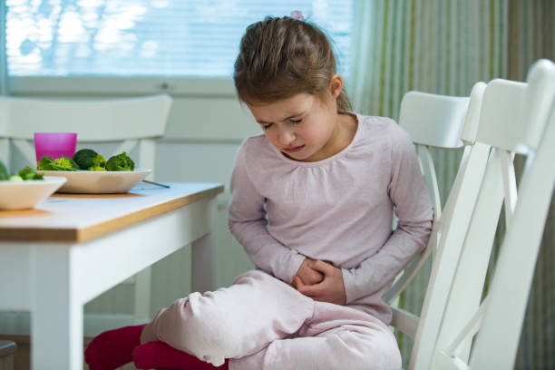 Child sitting at the table in the kitchen with stomach pain. stock photo